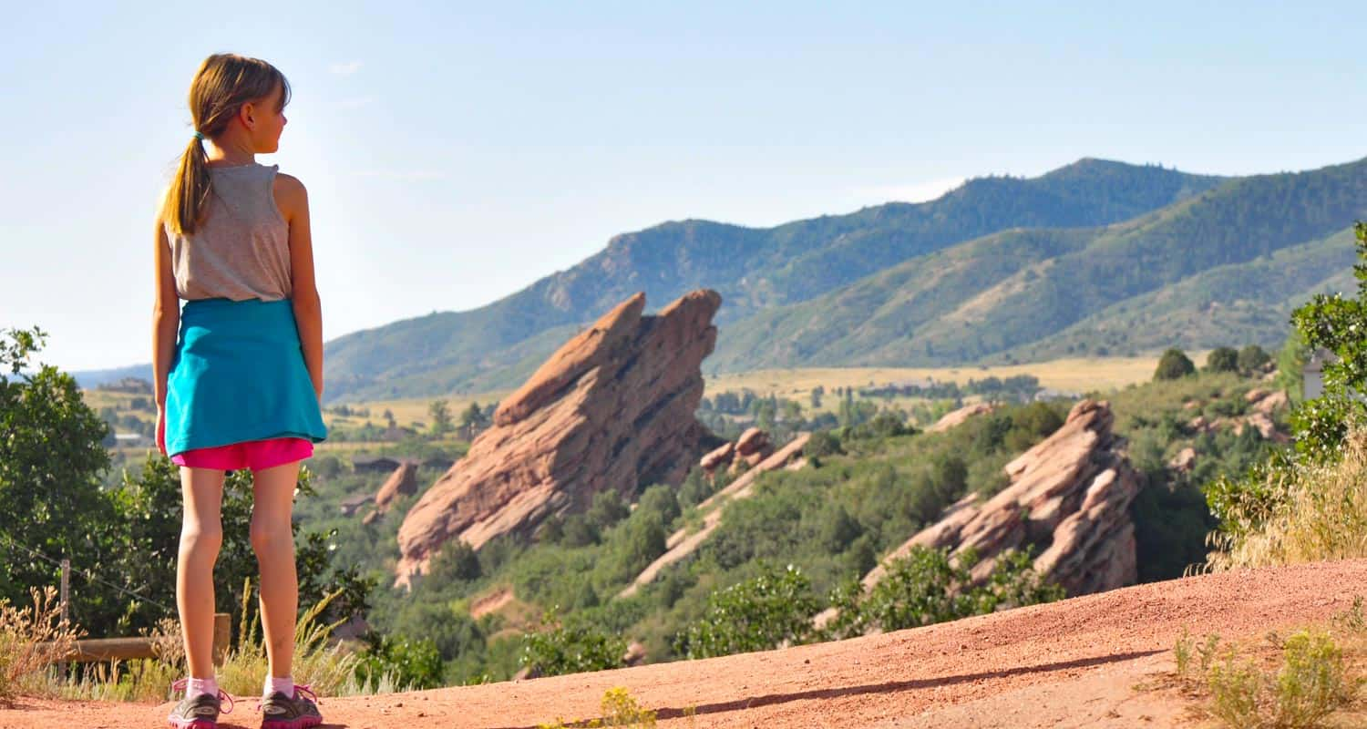 young hiker standing on trail with red rock formations and foothills in background in south valley park hike near littleton colorado