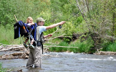 aaron johnson author of dayhikes near denver with daughter in backpack flyfishing on bear creek at Lair o the Bear Park near morrison colorado