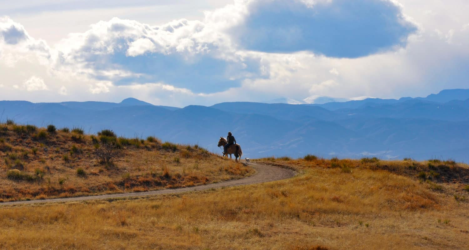 man on horse with dog on bluffs regional park trail with front range mountains in background on hike near denver