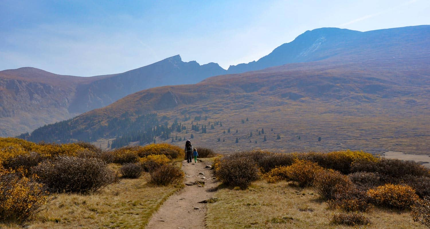 hiker and child on mt bierstadt trail with mountains in background hike near denver