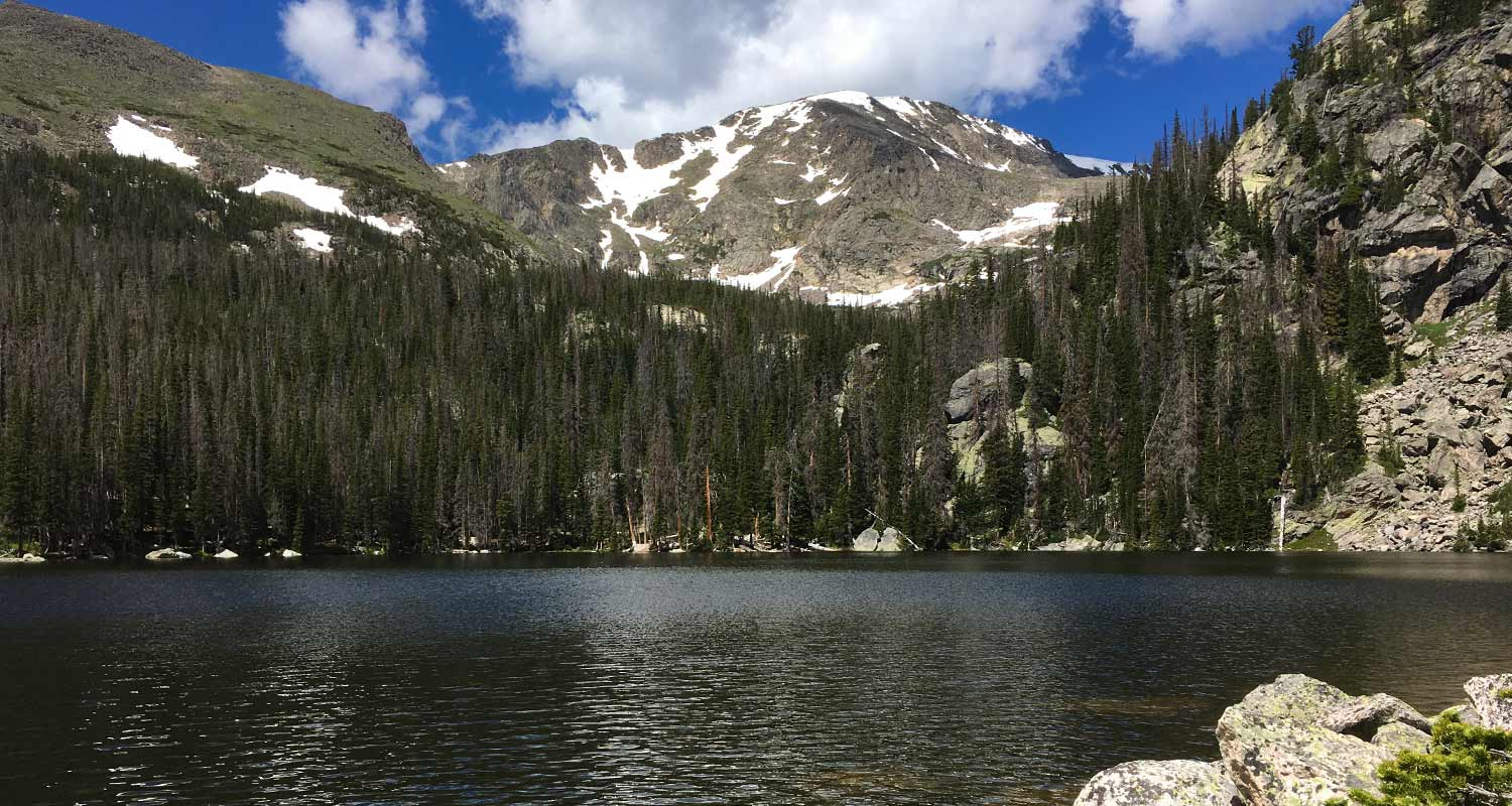 alpine lake with mount ypsilon in background with blue skies and clouds in rocky mountain national park hike