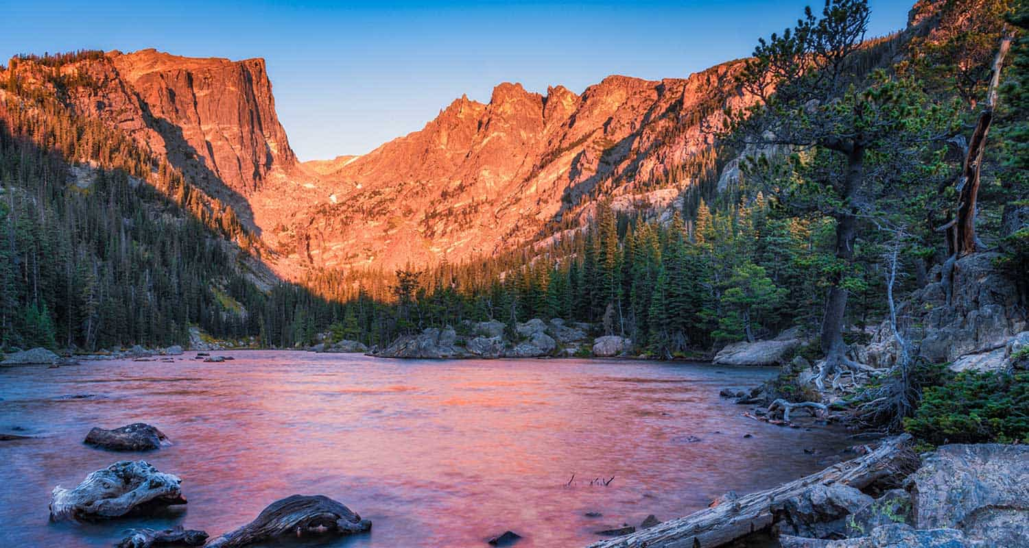 dream lake at sunrise in rocky mountain national park with mountain face of hallett peak in background