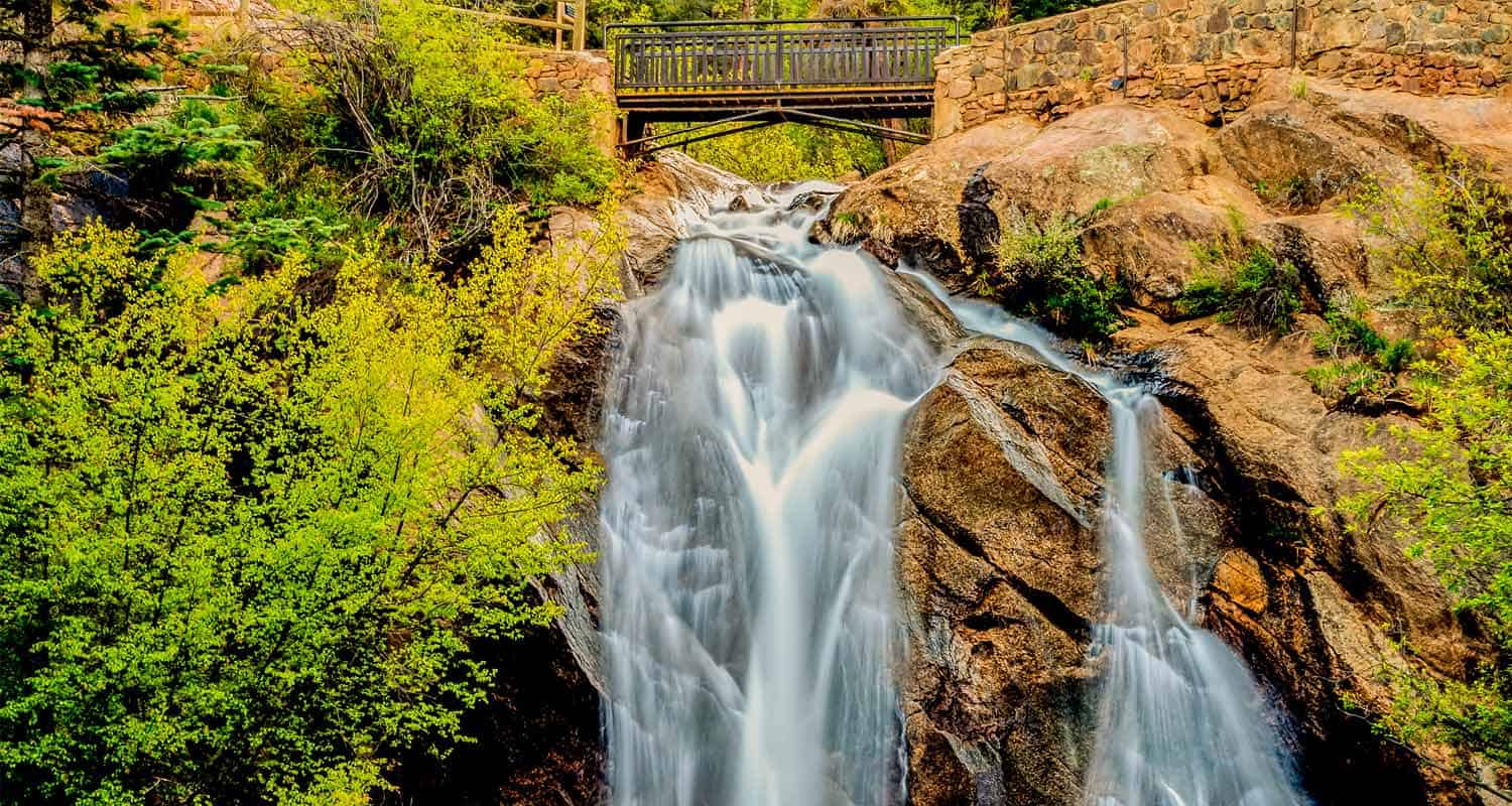 helen hunt falls waterfall pouring over granite rock face with bridge in background along hike near colorado springs