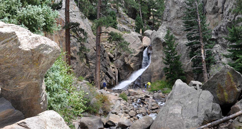 Boulder falls near boulder colorado in canyon with ponderosa pines and visitors at base of falls