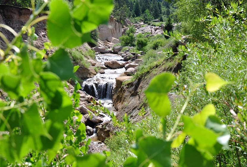 cherry creek waterfall flowing through Castlewood Canyon State Park with cottonwood leaves in foreground on hike near denver colorado
