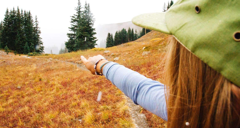 girl hiker in green hat pointing direction along mountain trail easy beginner hikes near denver