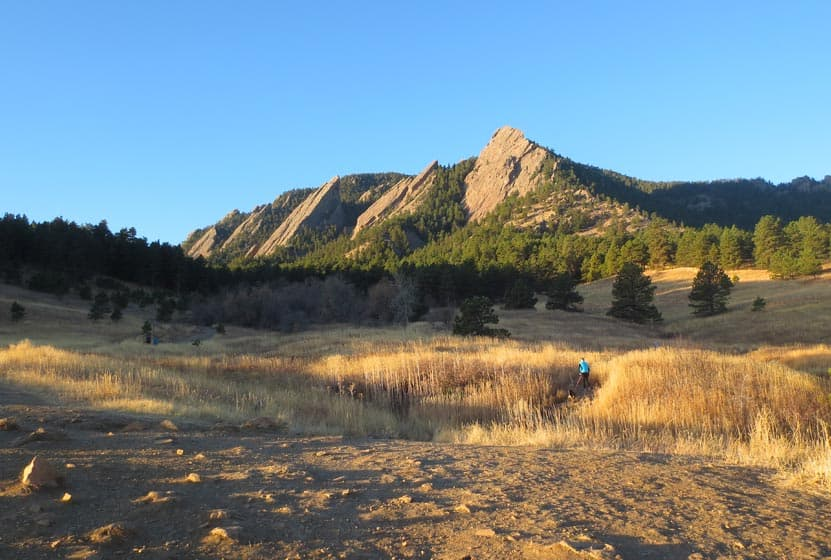 hiker in foreground on trail near Denver at chautauqua park with flatirons mountains in background and blue sky