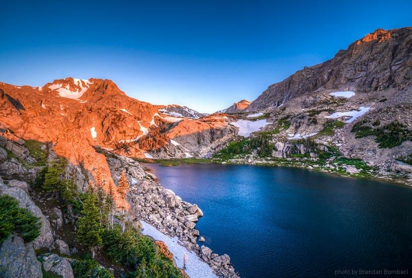Wild Basin in Rocky Mountain National Park sunrise on rock of deep blue lake on hike near denver colorado