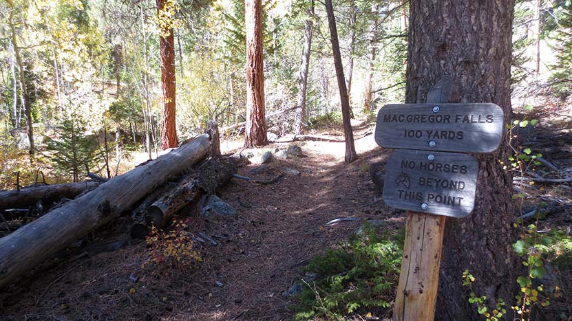 trail with sign for macgregor falls trail segment in mcgregor falls waterfall rocky mountain national park