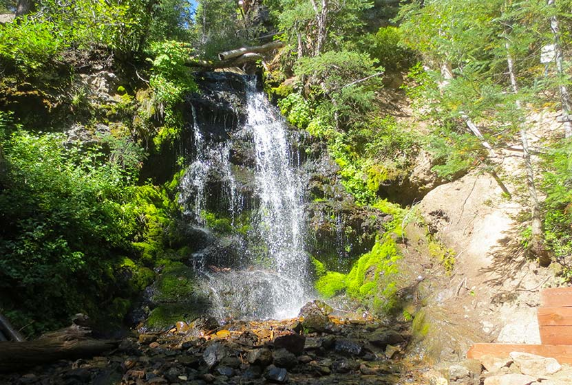 waterfall pouring over moss in wooded area near granby colorado