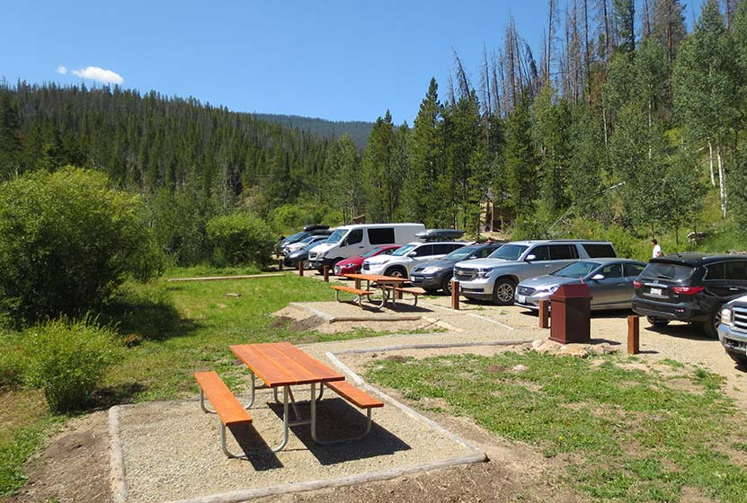 trailhead with picnic bench and cars for pole creek falls