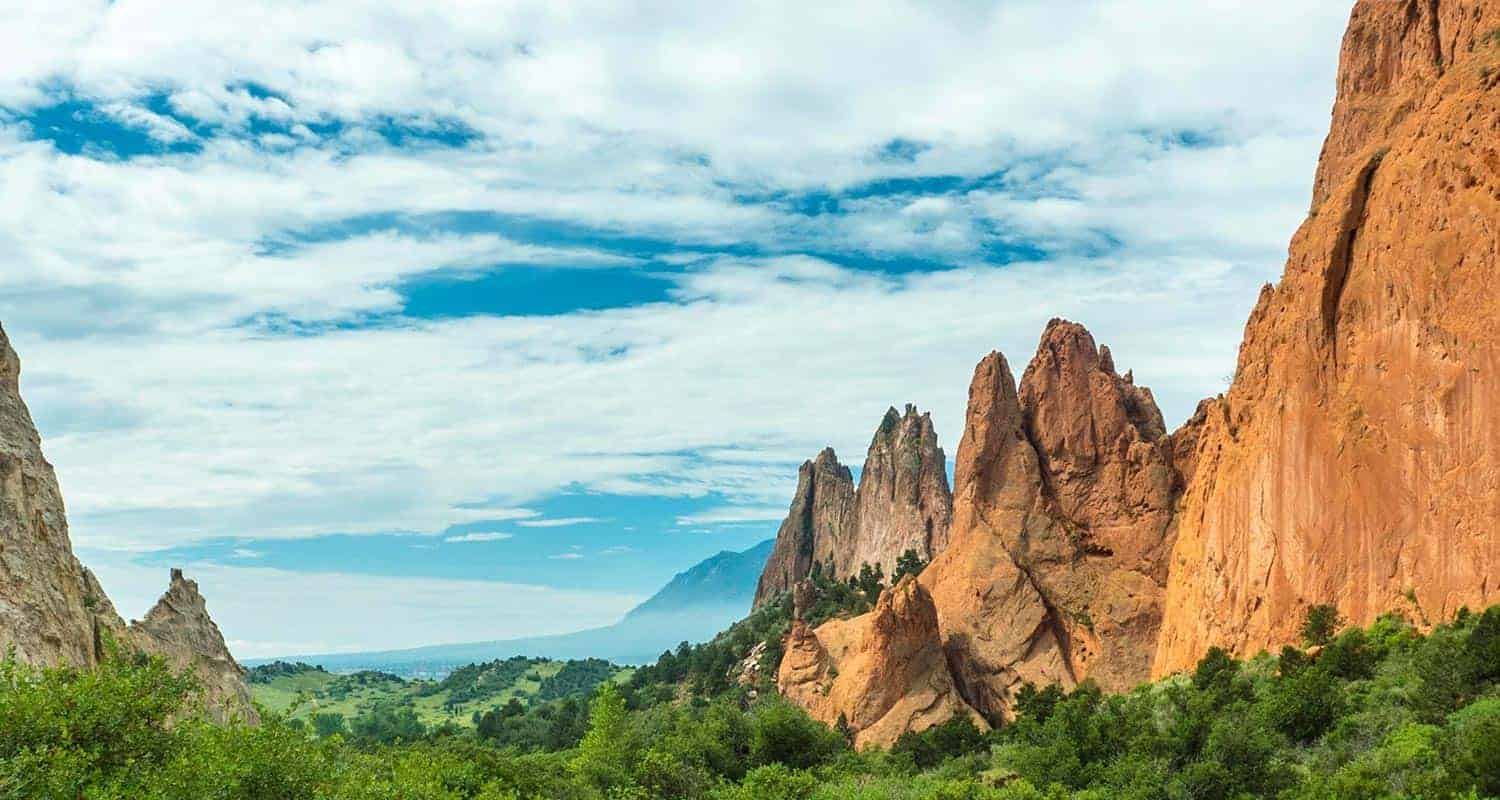 blue sky and clouds with orange towers of red rock in foreground at garden of the gods colorado springs hike