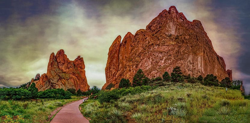 concrete path winding through red rock formations with scrub grasses and juniper trees