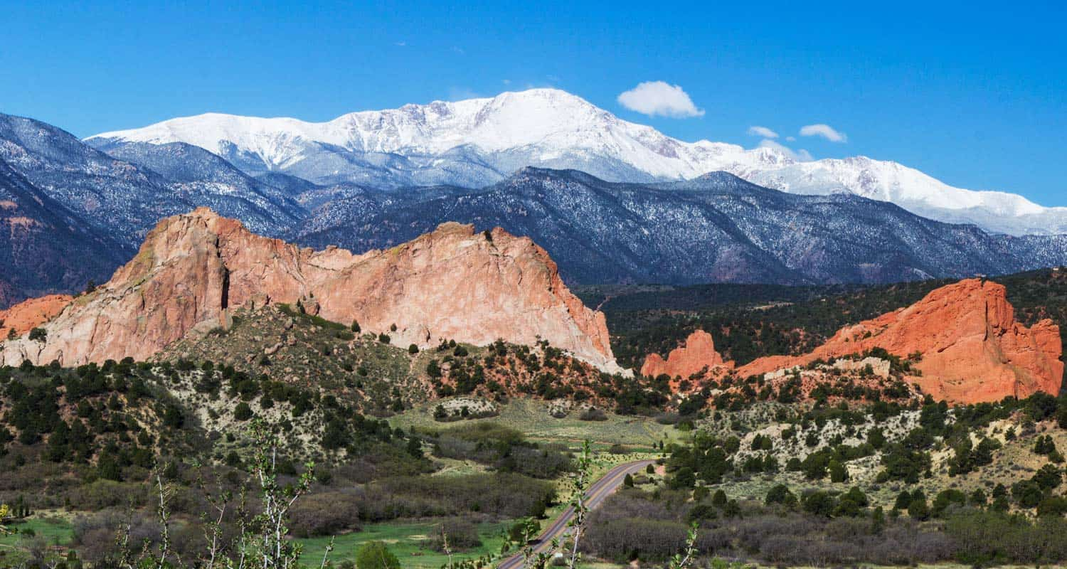 snow capped pikes peak in background and orange rock of garden of the gods in foreground