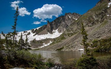 snow and evergreen trees on mountainside against blue clouded sky with Devils Thumb rock formation and lake