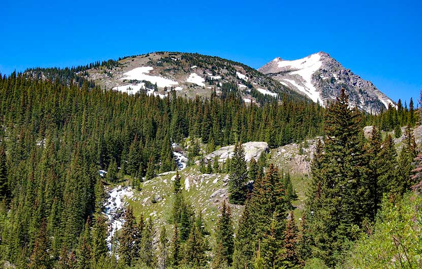 mountain peaks with late summer snow and cascading creek through high mountain meadow in indian peaks wilderness near jasper lake and devils thumb lake