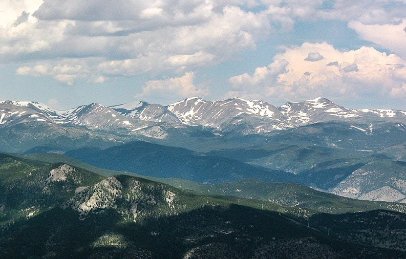 green mountains in front of snowcapped mount evans panoramic view with clouds from an top of chief mountain colorado