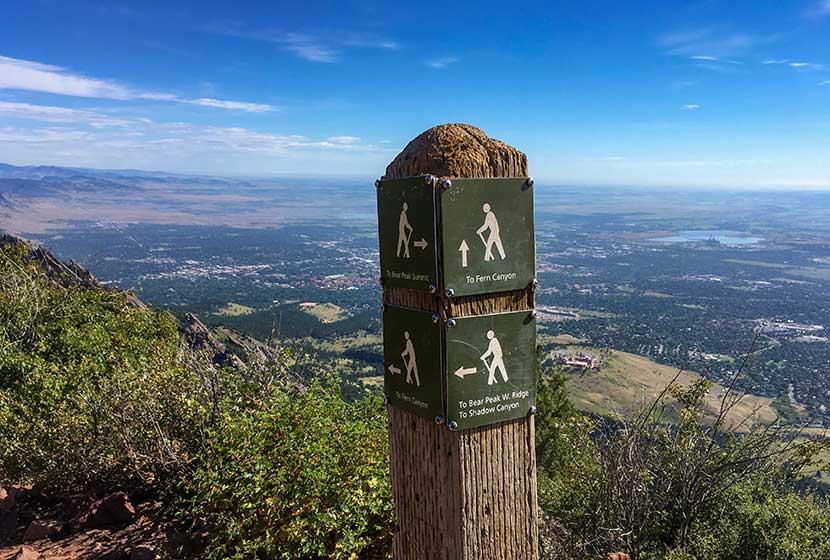 trail sign at split just below the summit of bear peak pointing to fern canyon