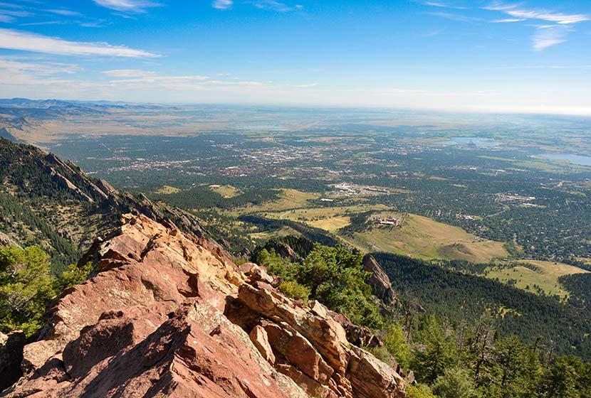 View from Bear Peak Near Boulder Colorado Orange granite peak looking down toward rolling green and trees landscape