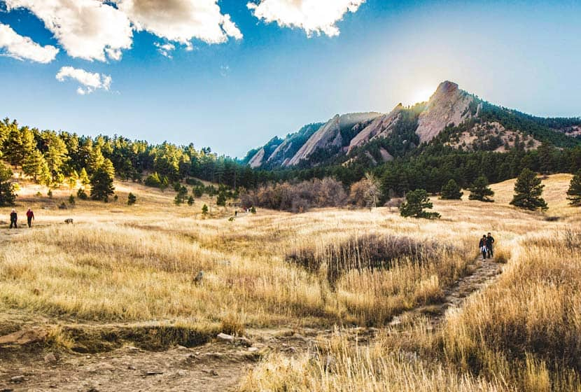flatiron mountain formation in boulder colorado with golden meadow and hikers on trails with sunset behind mountains