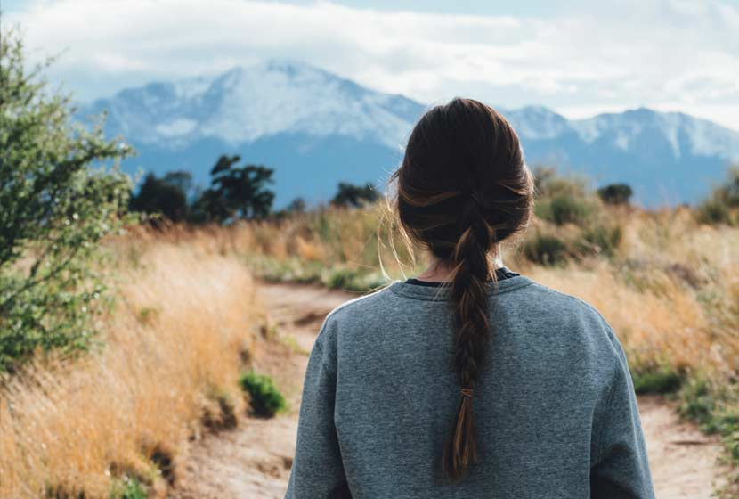 woman on hiking trail looking out to snowcapped colorado mountains