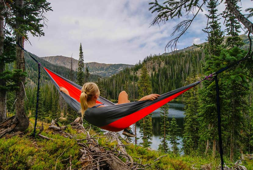 woman in hammock overlooking mountain lake with mountains in background hikes near denver