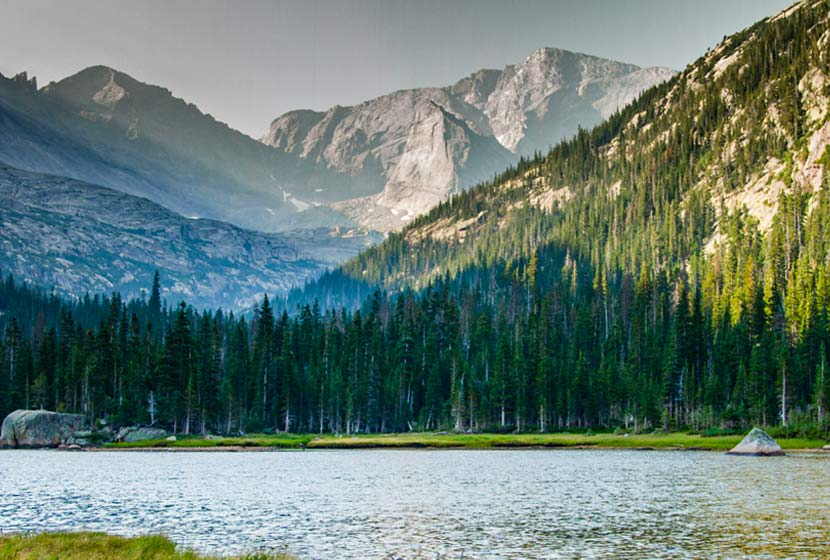 jewel lake in rocky mountain national park lake in foreground with morning light breaking onto mountain in middle ground and tall grey craggy mountain in background
