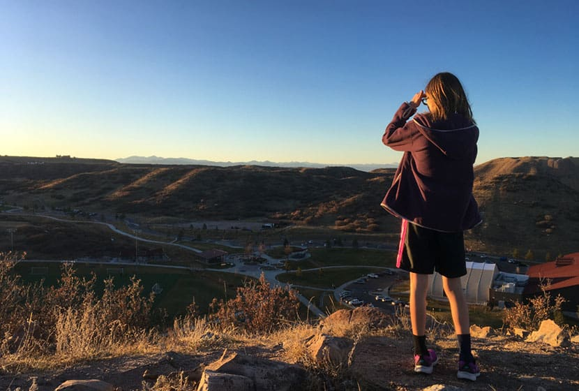 child looking west at sunset at the top of the castle rock incline