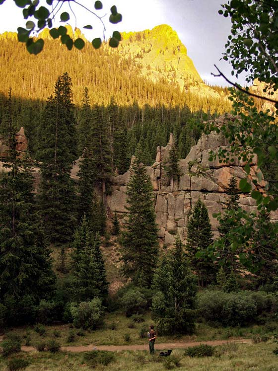 trail along the crags hike near colorado springs with hiker and dog below on trail and sunlit rock formation above cliffs in top of photo