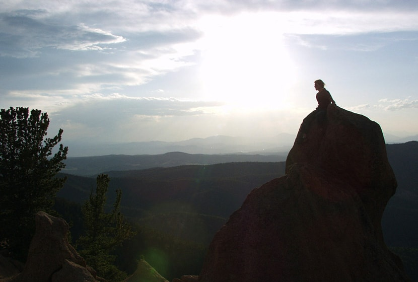 hiker looking toward mountains on rock formation at crags trail near colorado springs