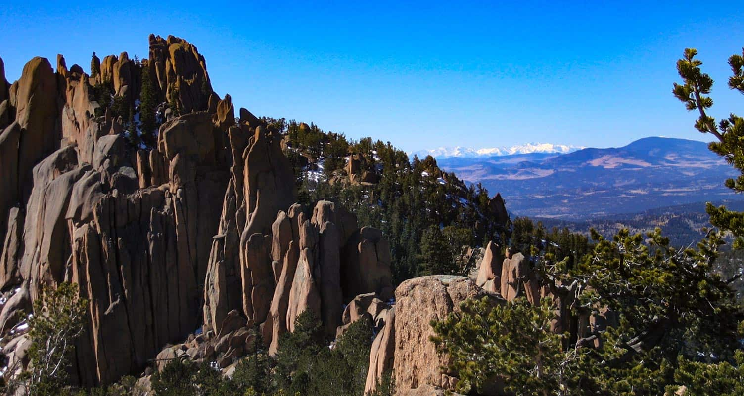 crags hike spires of pink granite with snowcapped mountains in background and pine trees in foreground