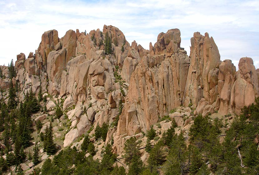 rock pinnacles at the crags hike near colorado springs pink and orange granite with evergreen trees in foreground