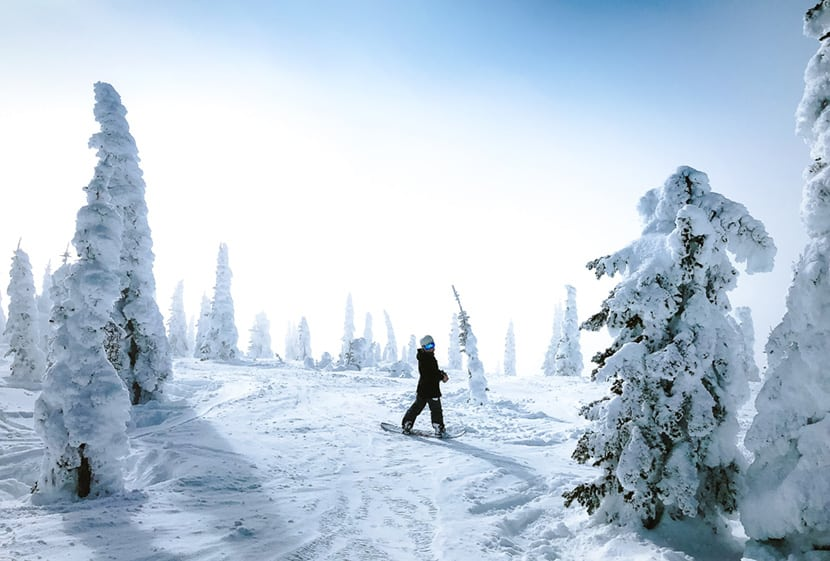 snowboarder on mountain ridge by colorado adventure photographer holly mandarich