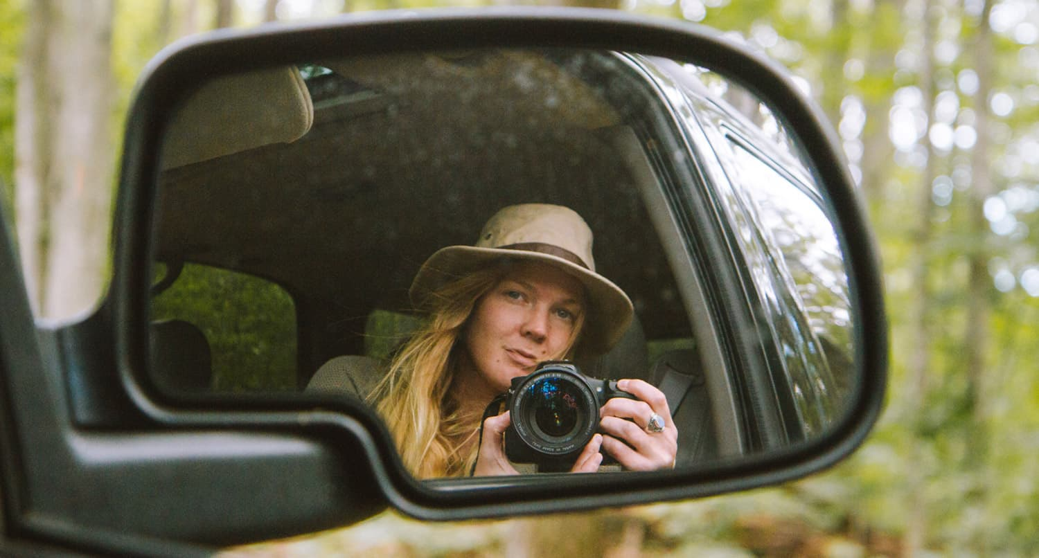 Holly Mandarich Adventure and Lifestyle Photographer reflection in car mirror driving along aspen grove