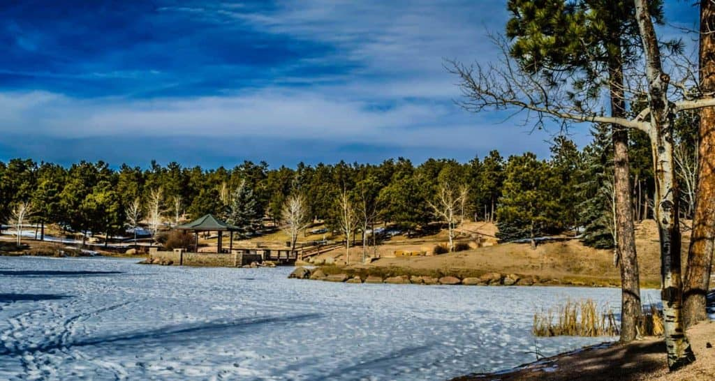 swan lake frozen over with pines and aspen trees at fox run park near colorado springs fallen timbers loop hike