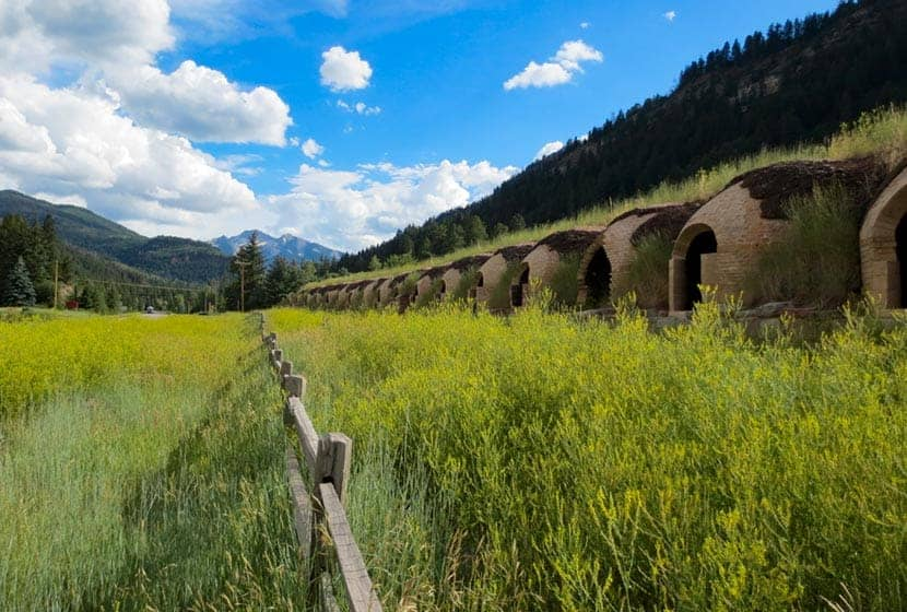 historic coke ovens with fence in foreground and mountain in background with lush green summer vegetation in redstone colorado