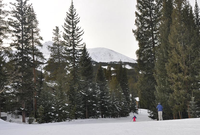 mom and daughter skiing cross country with breckenridge mountains in background on groomed trail at breckenridge nordic center