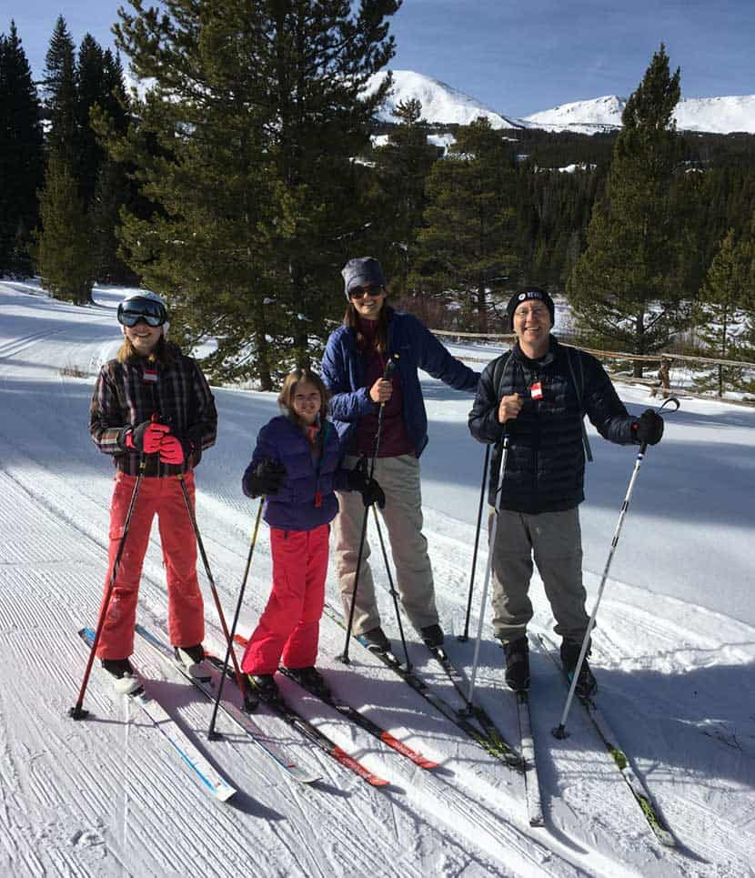 johnson family after ski lesson in breckenridge colorado with mountains in distance on groomed nordic trail