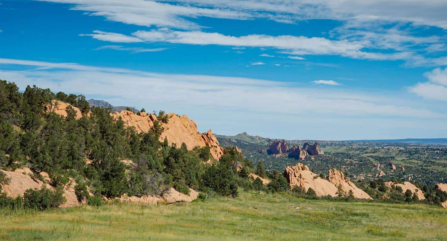 Hike at Red Rock Open Space in Colorado Springs looking North across meadow to Garden of the Gods in the distnce