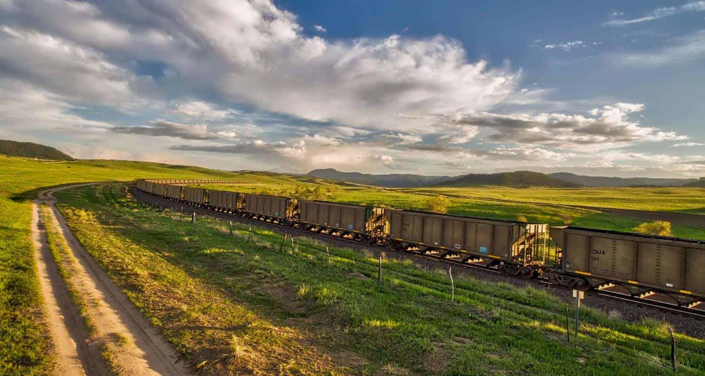 santa fe train running through green plains of greenland open space in colorado