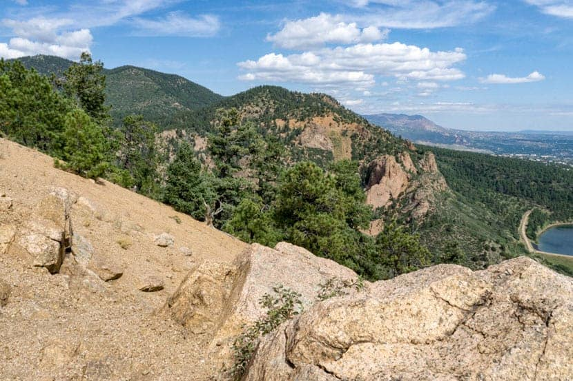 view from the summit of mt. cutler with granite rock in foreground and foothills in background near colorado springs