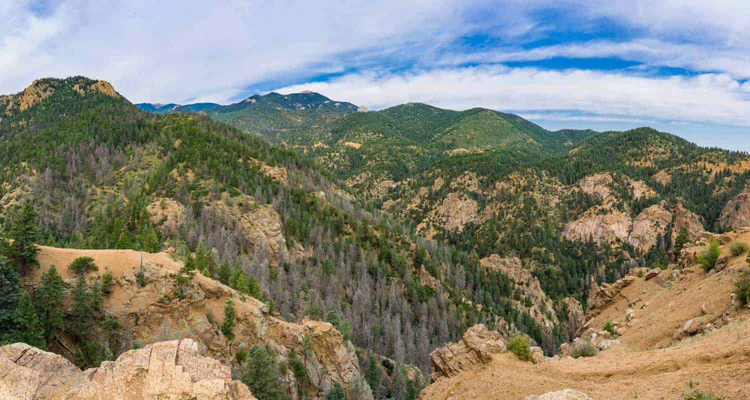 view from the summit of mt culter hike near colorado springs with yellow granite rock and green foothill mountains