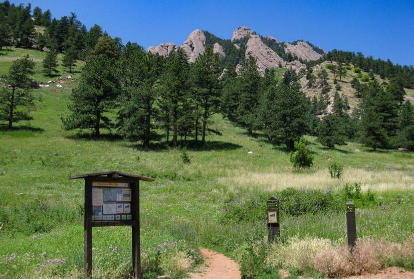 intersection of mesa trail and mallory cave trail in boulder with flatirons in background and trail sign in foreground