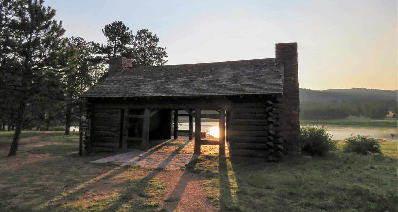 morning light breaking through old log cabin shelter at manitou lake