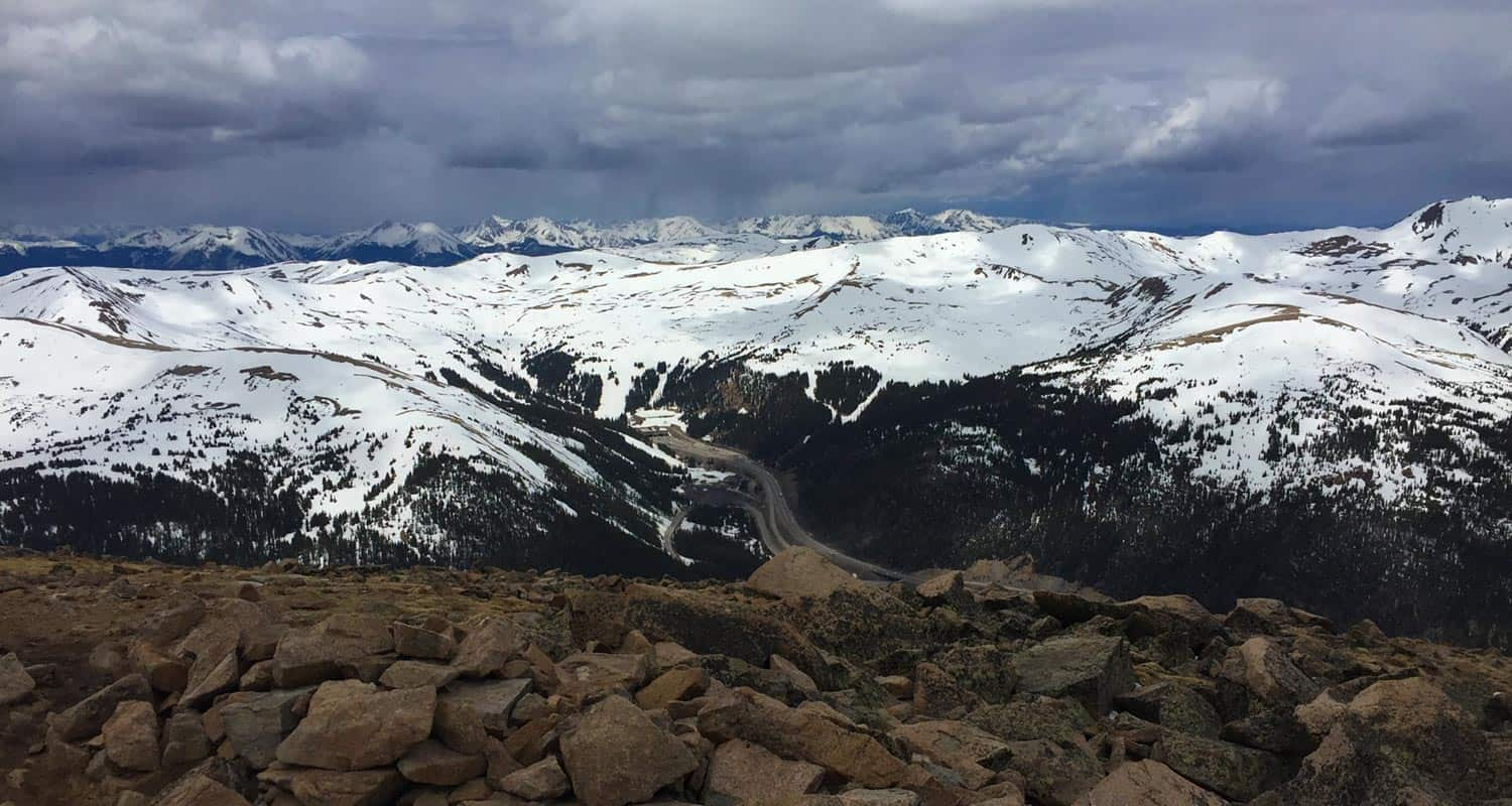 view from the summit of mt sniktau looking toward interstate 70 and weather rolling in on hike near denver
