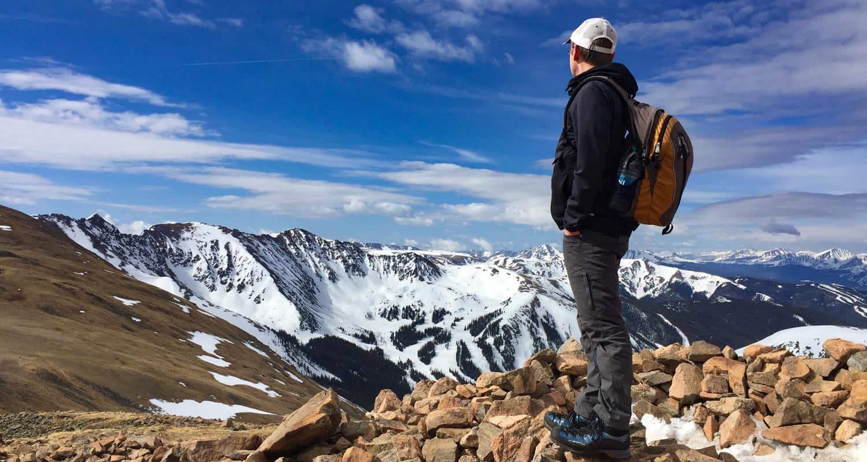 hiker near loveland pass colorado looking southwest toward snowcapped rocky mountains